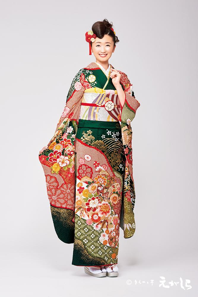 人気の濃い緑地色に御所車や雪輪などの古典柄を浮かべた、豪華絢爛な振袖。細やかな絞りに金駒刺繍、相良刺繍など、さまざまな技法を駆使して仕上げました。